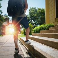 jongen met rugzak in de zon aan een trap